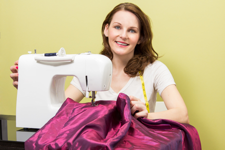 Brunette european woman sewing diy at home in front of yellow background photo