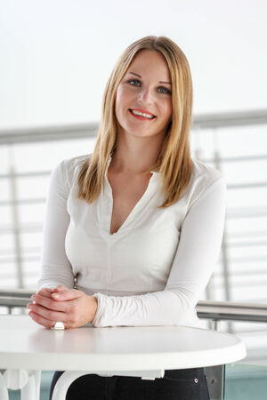 personable: Businesswoman standing in a modern Building with a white shirt and black pants