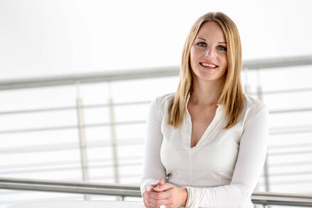personable: Businesswoman standing in a modern Building with a white shirt Stock Photo