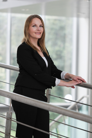 Businesswoman standing in a modern Building with a black jacket and black pants photo