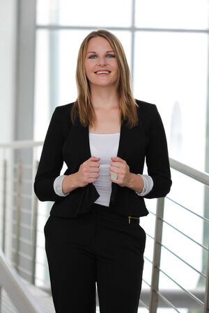 blazer: Businesswoman standing in a modern Building with a black jacket and black pants