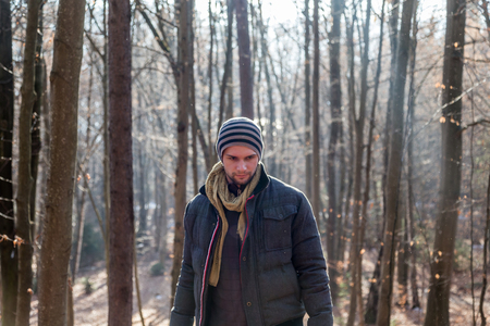 Man standing in the forest during wintertime with a thick jacket photo
