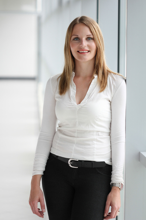 Businesswoman standing in a modern Building with a white shirt and black pants photo