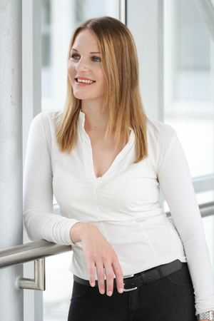 Businesswoman standing with a white shirt and black pants photo