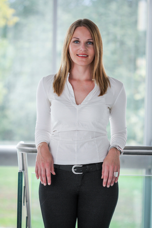 black pants: Businesswoman standing in a modern Building with a white shirt and black pants
