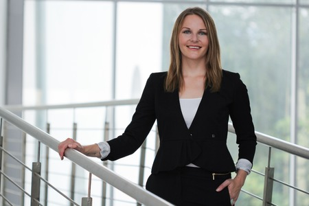 Businesswoman standing with a black jacket and black pants photo