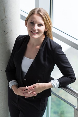 Businesswoman standing in a modern Building with black jacket and black pants photo