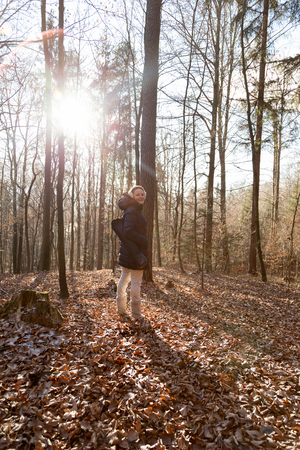 Woman standing in the forest during wintertime with a thick jacket photo