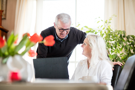 them: Older couple having fun and smiling while working from home on notebook with green flowers and window light around them