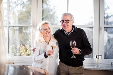 clinking: Older good looking and handsome couple drinking champagne at home and clinking glasses