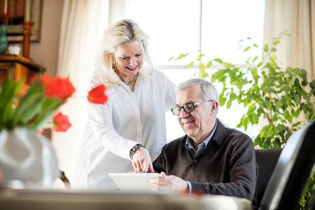 hombres trabajando: Pareja de más edad que se divierten y sonriendo mientras se trabaja desde su casa en el cuaderno con flores verdes y luz de la ventana a su alrededor