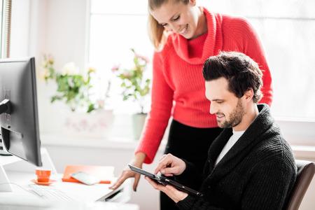 trabajando en casa: Pares que trabajan en la oficina en casa con el teléfono y el ordenador