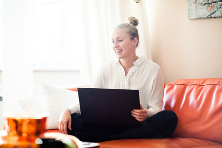 woman couch: Woman working from home on her relaxing orange couch Stock Photo