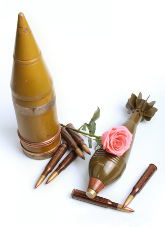 bomb mortar and bullets with a rose laying on top