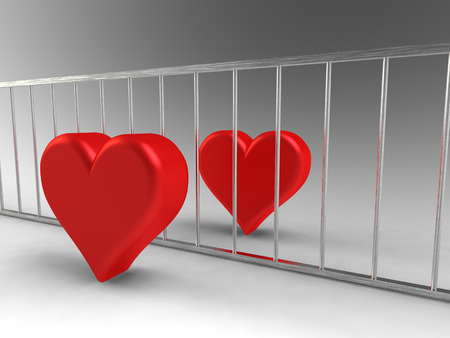 Two hearts seperated by metal bars Stock Photo