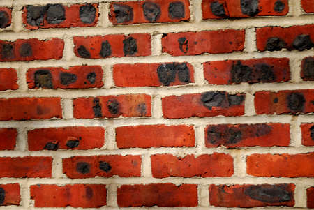 An old brick wall with interesting texture and dark black marks.