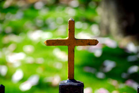 A yellow cross sitting on top a black fence