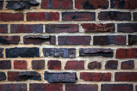 An old brick wall with interesting texture and dark black marks