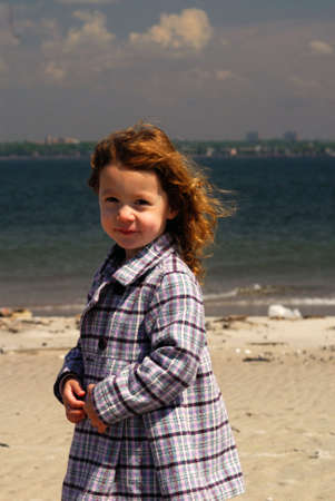 A little girl posing on a sunny beach. Stock Photo