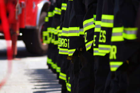 A photo of NYC firefighters line up with the backs of their coats showing Foto de archivo