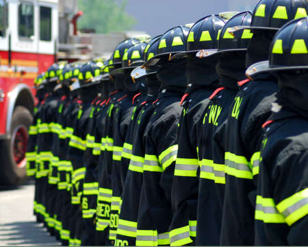A photo of NYC firefighters line up with the backs of their coats showing photo