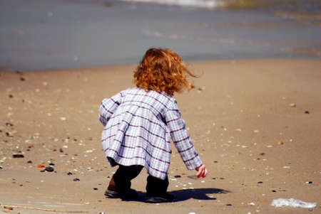 A little girl picking up a white sea shell on a beach Stock Photo