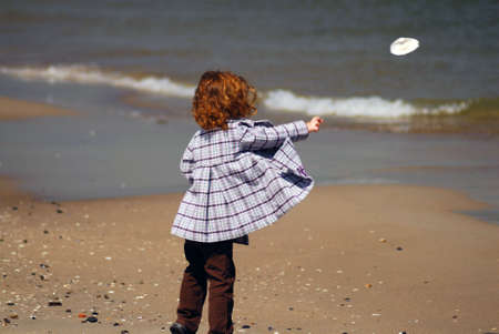A little girl standing on a beach throwing a sea shell into the water Stock Photo