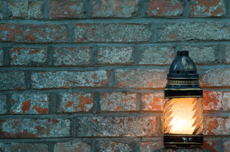 Candle on a brick background with copy space photo