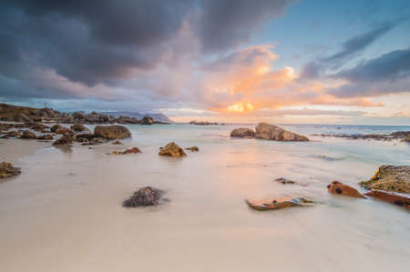 vibrance: Long exposure photography of waves crashing over rocks at sunrise with storm clouds building