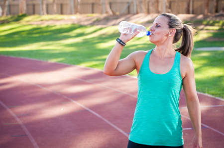 athletics track: a female athlete drinks from a bottle of water while standing on an athletics track Stock Photo