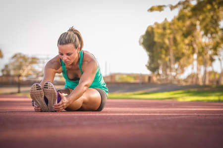 vibrant image of a female athlete stretching on a running track