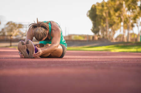 female athlete: vibrant image of a female athlete stretching on a running track