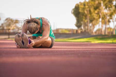 deportista: vibrante imagen de un atleta de sexo femenino que estira en una pista de atletismo Foto de archivo