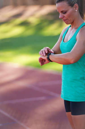 individual sport: A female athlete at a running track adjusts her heart rate monitor before a workout