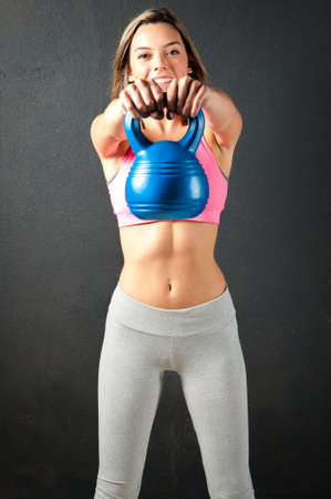 kettle bell: Attractive female fitness model isolated on a black background in sports wear background in sports wear with a kettle bell Stock Photo