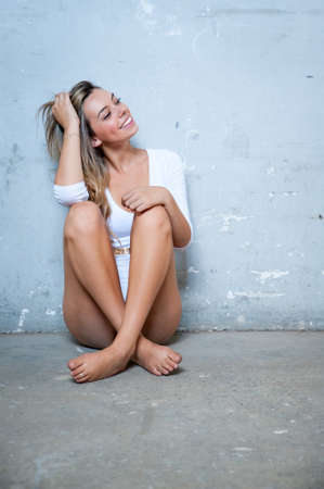 white body suit: Cute female girl sat in an abandoned building in a white body suit