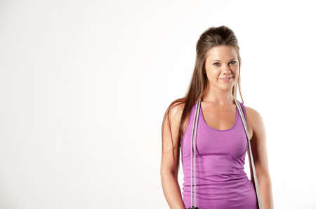 skipping rope: Attractive female fitness model isolated on a white background in sports wear with a skipping rope