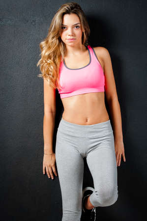 sports wear: Attractive female fitness model isolated on a black background in sports wear Stock Photo