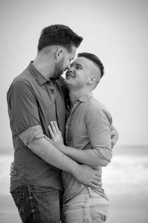 gay men lovingly embracing and cuddling on a beach