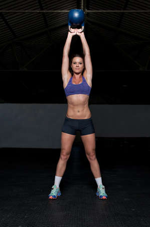 Muscular Woman doing kettle bell exercise in a dark gym Stockfoto