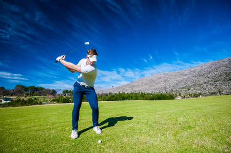 Close up image of a male golfer playing a shot on the fairway on a golf course in south africa Stockfoto