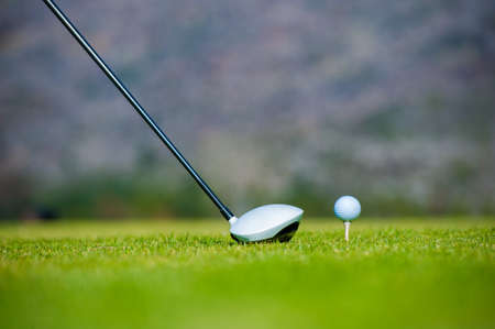 off course: view of a golfer teeing off from a golf tee on a bright sunny day on a golf course in south africa