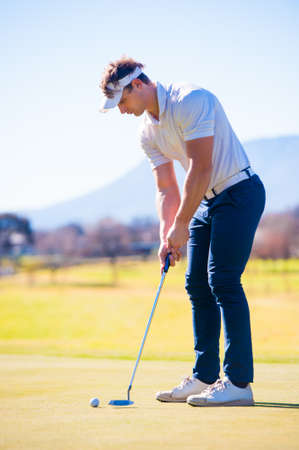 Close up view of a golfer planning his shot to the pin on a green on a bright sunny day Stock Photo