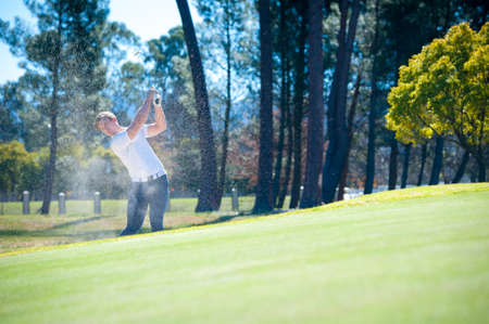 shot: image of a golfer playing a chip shot onto the green on a golf course in south africa Stock Photo