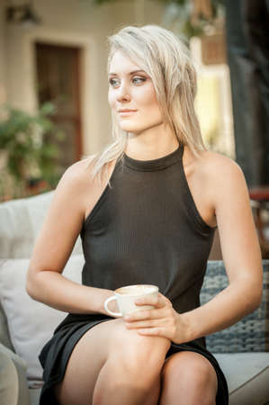 blonde twenty something girl holding a coffee cup