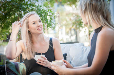 two pretty blonde sisters sat on a sofa outside enjoying a coffee Stock Photo