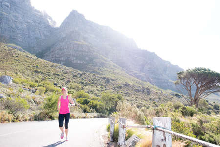 Wijfje dat langs een weg met de berg van de Kaapstedenlijst op de achtergrond loopt Stockfoto