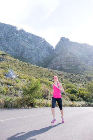 vrouw loopt langs een weg met Kaapstad's tafelberg op de achtergrond