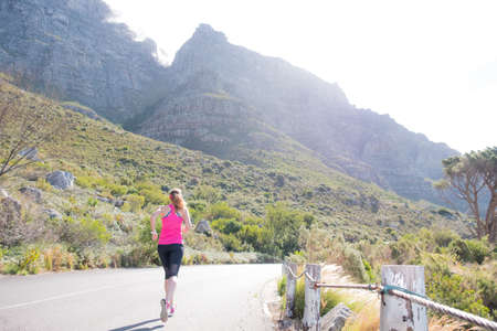 female running along a road with cape towns table mountain in the background