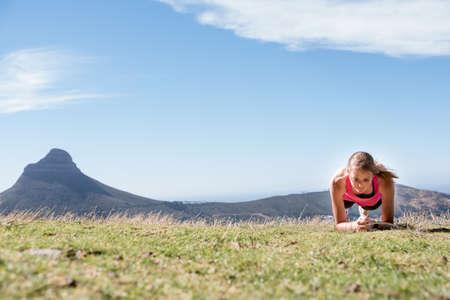 atletisch wijfje dat een plank in openlucht met leeuwenhoofd en Kaapstad op de achtergrond doet